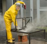 Frau in gelber Arbeitskleidung mit Gesichtsschutz führt Prüfung mit Hochdruckstrahler durch